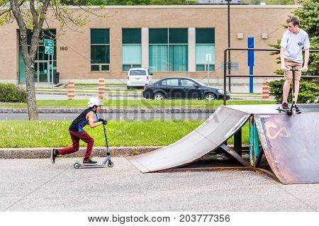 Saguenay, Canada - June 3, 2017: Downtown City Summer Park In Quebec With Young Teenagers Boys Skati
