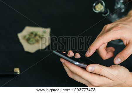 man using a smartphone. Bong and medical marijuana, cannabis thc flower Sativa and Indica Close up on a black background. lifestyle Concepts the legalization of marijuana in the world poster
