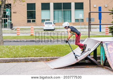 Saguenay, Canada - June 3, 2017: Downtown City Summer Park In Quebec With Young Teenager Boy Sliding