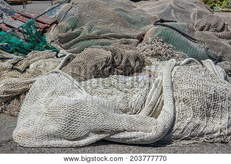 Pile of commercial fishing nets applied to the soil of a port