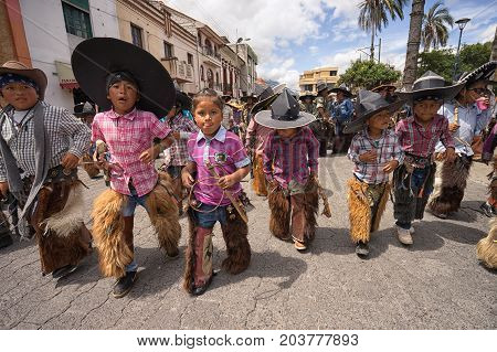 June 25 2017 Cotacachi Ecuador: children wearing sombreros and chaps at the Inti Raymi celebrations