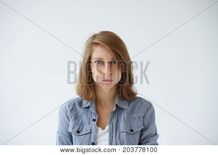 Portrait of displeased grumpy young woman with blue eyes and freckles grimacing blowing her cheeks feeling angry and furious losing her temper. Negative reaction annoyance anger and bad mood