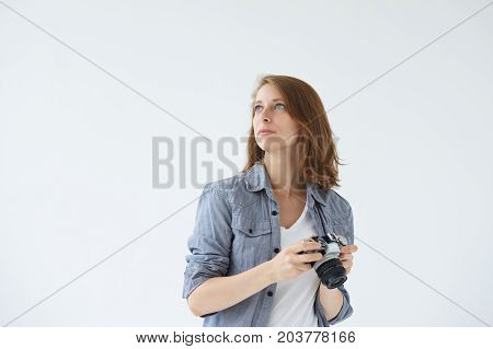 Waist up shot of self-employed female stock photographer working in studio holding digital camera in her hands searching for best perspective and angle. People hobby profession and occupation