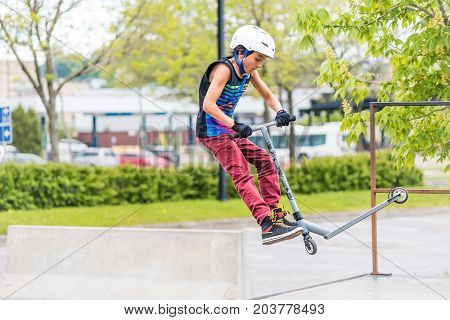 Saguenay, Canada - June 3, 2017: Downtown City Summer Park In Quebec With Young Teenager Boy Skating