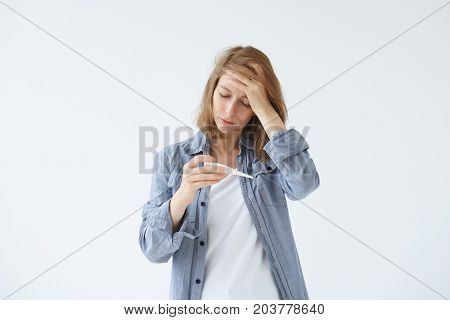 Picture of unhappy young woman holding thermometer in hands measuring body temperature while suffering from influenza. Frustrated female with thermometer touching her forehead feeling sick