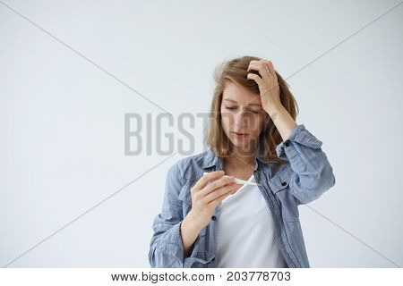Sickness illness disease ailment and health problems concept. Studio portrait of young female with painful stressed look holding thermometer running high temperature while suffering from fever