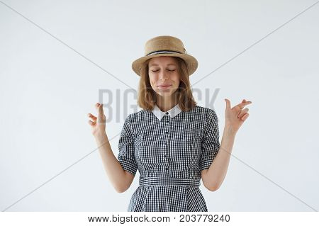 Picture of pretty girl in romantic dress and hat having excited superstitious and naive look keeping fingers crossed and eyes closed for good luck hoping her dreams will come true. Body language