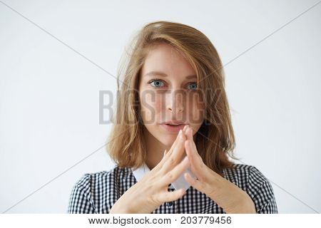 Human emotions and feelings. Attractive young woman with bob haircut clasping hands her look and gesture expressing impatience and worry. Cute girl feeling worried and frustrated posing in studio