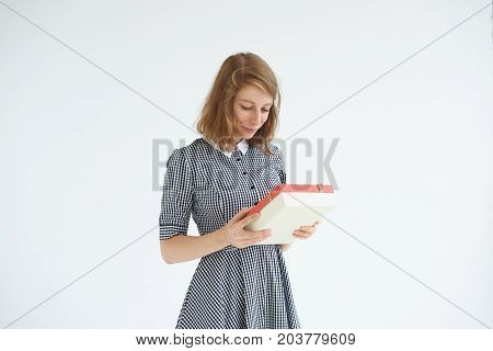 Portrait of charming young woman holding box of assorted chocolates sent to her by secret admirer having impatient and ancitipated look. Sweets dessert love romance and Valentine's Day concept