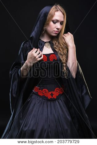 Blond young woman in black hood on black background