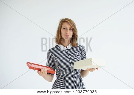 Sad unhappy young female standing at white wall with opened box of candies disappointed with bad taste of chocolates. Frustrated woman feeling worried after she ate a lot of high-calorie sweets