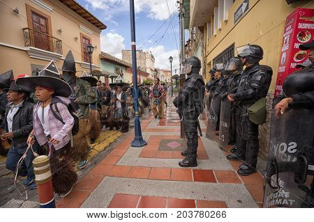 June 25 2017 Cotacachi Ecuador: riot police standing by as the male dances run down the street towards the main plaza