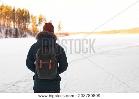 Fashionable hipster traveler with backpack wearing red hat and coat walking alone in winter snowy forest in search of silence and tranquility. People wanderlust travel hiking and adventure concept
