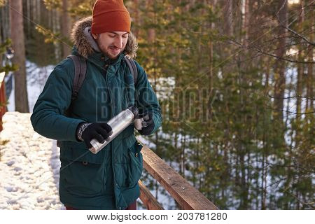 Picture of happy young bearded European backpacker wearing gloves hat and coat with fur hood drinking hot beverage outdoors while hiking in winter woods holding thermos of tea or coffee and mug