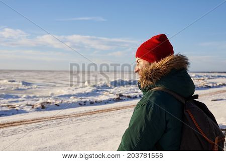 Handsome bearded man wearing red hat and coat with fur hood carrying backpack hitchhiking on road in rural area while traveling alone in winter. People lifestyle travel and trekking concept