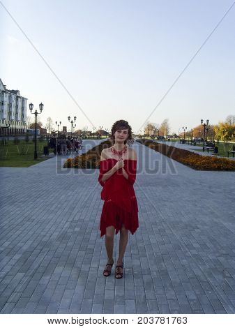 Girl In A Red Dress Posing For A Photographer. Beautiful Girl In Red Clothes.