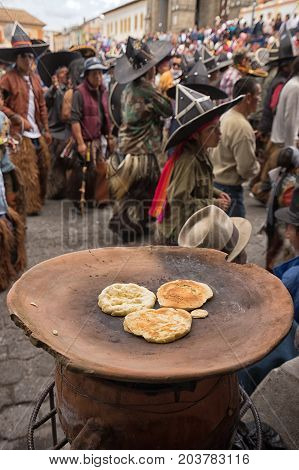 June 25 2017 Cotacachi Ecuador: corn based flat bread is being prepared by the side of the street on clay platter heated by wood fire at the Intin Raymi parade