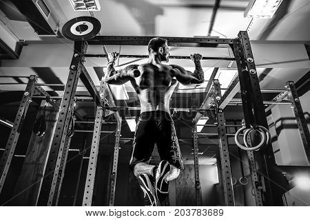 Strong shirtless man pulling up on horizontal bar in a gym.