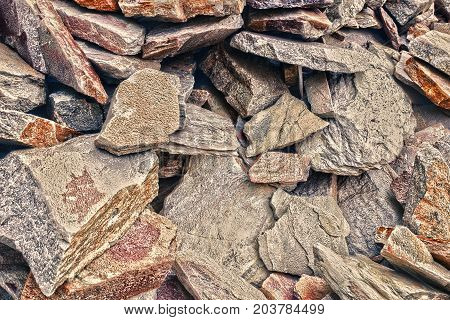 A big heap of sandstones, storage space of various natural sandstone. Cracks and colorful layers of sandstone background. The pattern of the variegated sandstones. Layers of toning colored stones