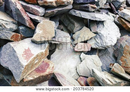Cracks and colorful layers of sandstone background. A big heap of sandstones storage space of various natural sandstone. The pattern of the variegated sandstones. Layers of toning colored stones