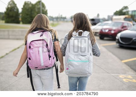 Portrait of two pre teenage girls studying outdoors in school yard