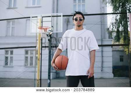 Young and strong basketball player is standing on the playground. He wears white t-shirt and black pants. This guy is holding the ball with his right hand.