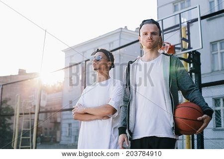 Two basketball players are standing at the small stadium in a sunny day. One of them holds the ball with his hand and looking straight to the camera while the other one is standing further away, keeping his hands crossed and looking aside. Close up