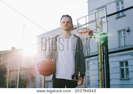 The portrait of a young man that stands near the basket in a bright sunny day. He is holding the ball for the basketball game with his right hand. He is looking straight to the camera.