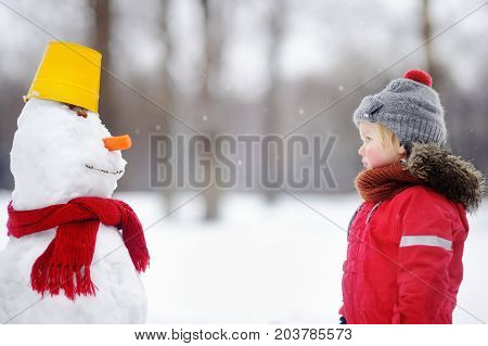 Little Boy In Red Winter Clothes Having Fun With Snowman