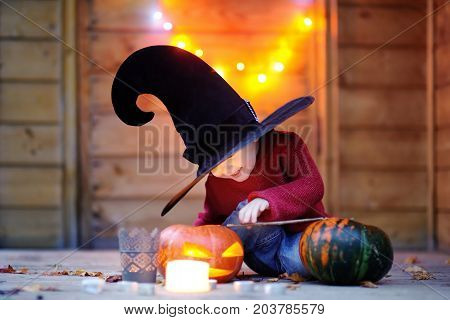 Cute Little Wizard With Magic Wand And Jack-o-lanterns