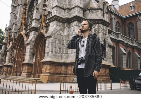 The ambitious and curious traveller is standing on the road near the old church building. He is talking on his phone with somebody and looking straight forward. He is very serious and concentrated.
