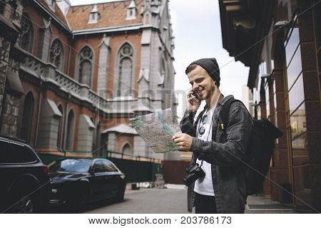 Young photographer that likes to travel is checking his current location during the phone call . He has found the right place to go so that's why he is happy and smiling.