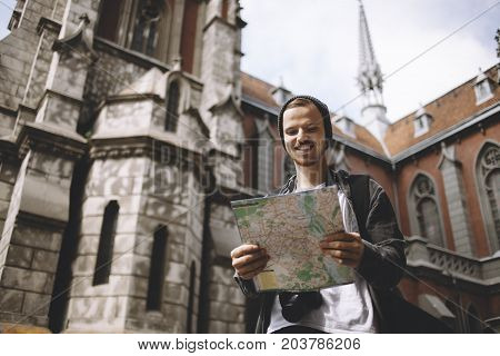 The picture of a traveller that is standing near the church. He is holding the map in his hands. He has found the place where he wants to go. This guy looks happy. Cut view