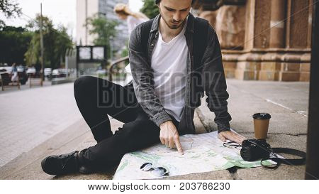 Close view of a young hipster that likes to travel. He decided to have some rest and sit down on the cathedral's steps on the street. His coffee is getting colder while the guy is stading the map of the city. Close up