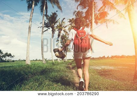 Young active girl with outspread hands walking at sunny day near palm trees intentional sun glare