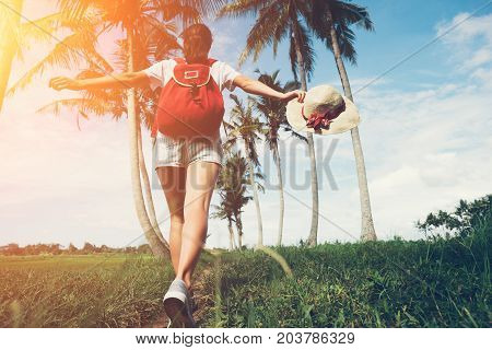 Young and active girl with outspread hands walking at sunny day near palm trees intentional sun glare