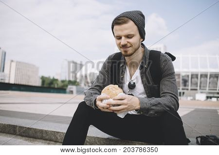 The close view of a hungry traveller sitting on the steps on the street in a beautiful sunny day. His trip is over but not his lunchtime. The guy is ready to start eating his meal. Cut view