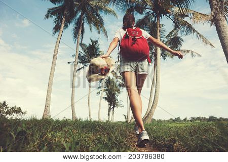 Young and pretty girl with outspread hands walking at sunny day near palm trees intentional vintage color