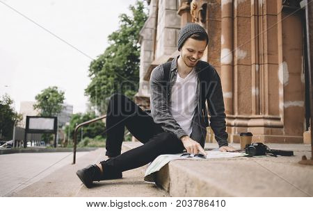 Happy and smiling tourist is sitting on the church's steps on the street. He took a cup of coffee and decided to have some rest. Now he is studing the map of the city. His camera is placed near the cup of coffee.