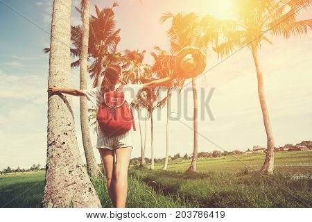 Young and pretty girl with outspread hands enjoying holidays in nature resort intentional sun glare and vintage color