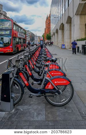 London UK - May 31 2017 Row of Santander Cycles ready for hire in High Holborn. with bus and cab passing on the road.