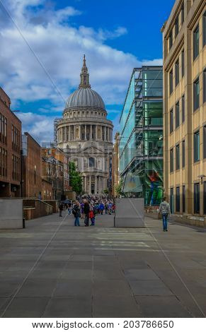 London UK - August 3 2017: Looking towards St. Paul's Cathedral from the Millennium Bridge. Shows crowds of tourists moving between St. Pauls and the Millennium Bridge.