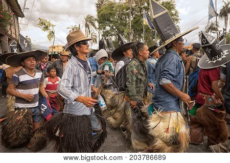 June 25 2017 Cotacachi Ecuador: indigenous quechua men wearing sombreros and chaps dancing at the Inti Raymi celebrations