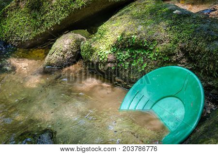 Gold pan resting in mineral rich riverbed. Fun and adventure in recreational outdoor activity of panning for gold and mining for gemstones.