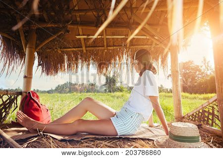 Young girl sitting and listening music with headphones in nature under straw roof intentional sun glare