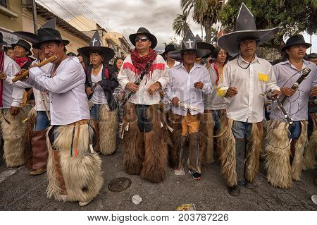 June 25 2017 Cotacachi Ecuador: at Inti Raymi celebrations men wearing furry chaps and oversized sombreros whistle chant and stomp in the streets of the indigenous town