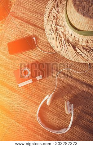 Mobile phone, vintage photo camera, headphones and hat lying on straw intentional sun glare