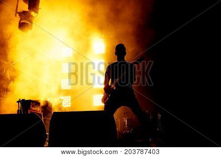 Silhouette of guitar player, guitarist perform on concert stage. Orange background, smoke, concert spotlights.