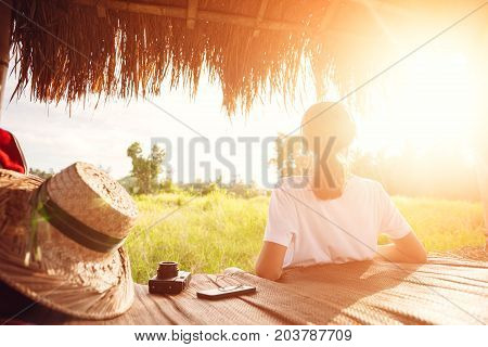 Young girl sitting and relaxing outdoors and listening music with headphones at good sunny day intentional sun glare