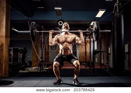 Muscular fitness man doing deadlift a barbell over his head in modern fitness center. Functional training. Snatch exercise